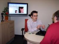 Akustikermeister Stefan Kraus passt einer Frau Hörgeräte an. Zu sehen ist das Anpassungsgespräch.
